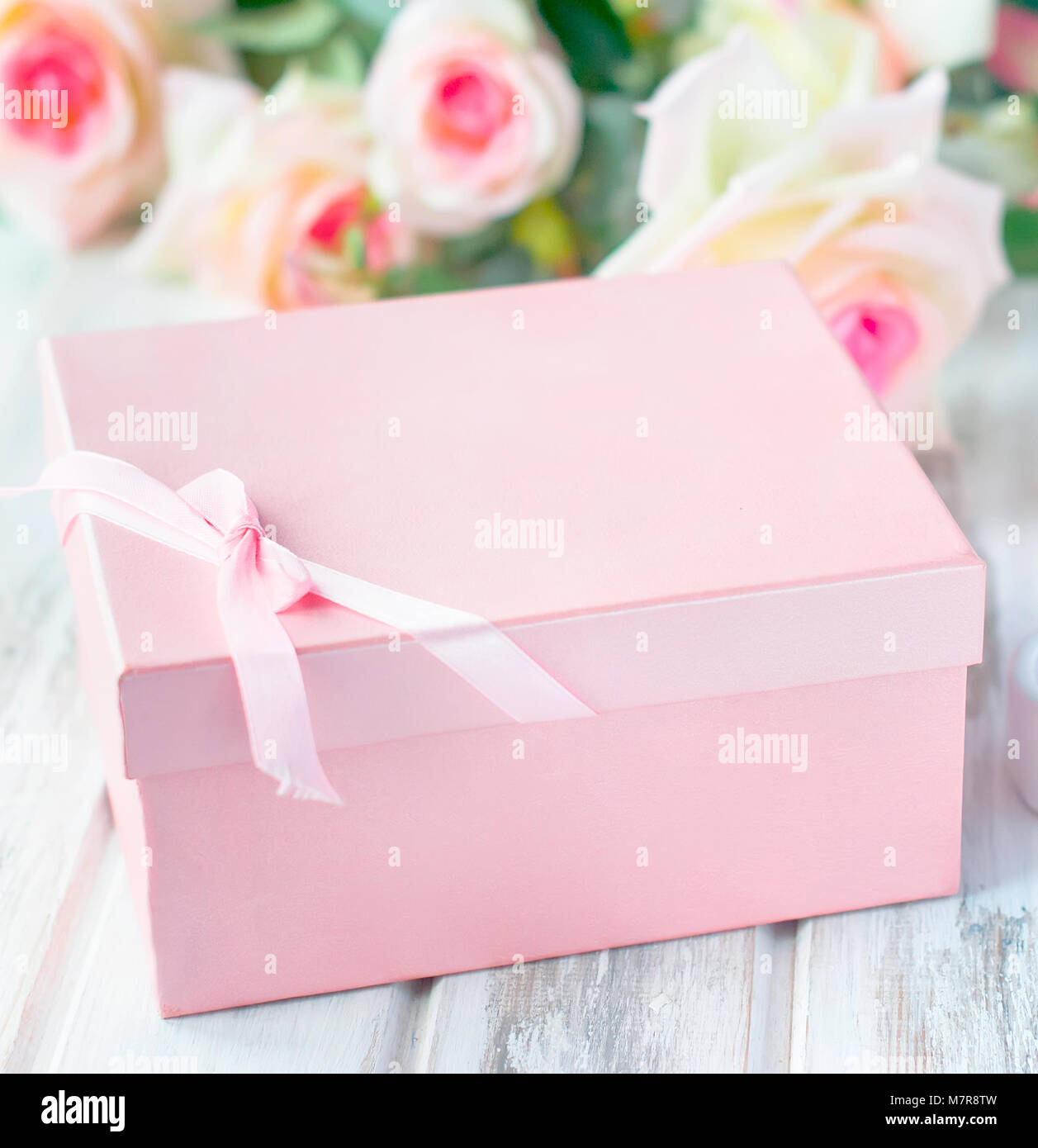pink gift box, candle and a bouquet of cream roses. holiday concept ...
