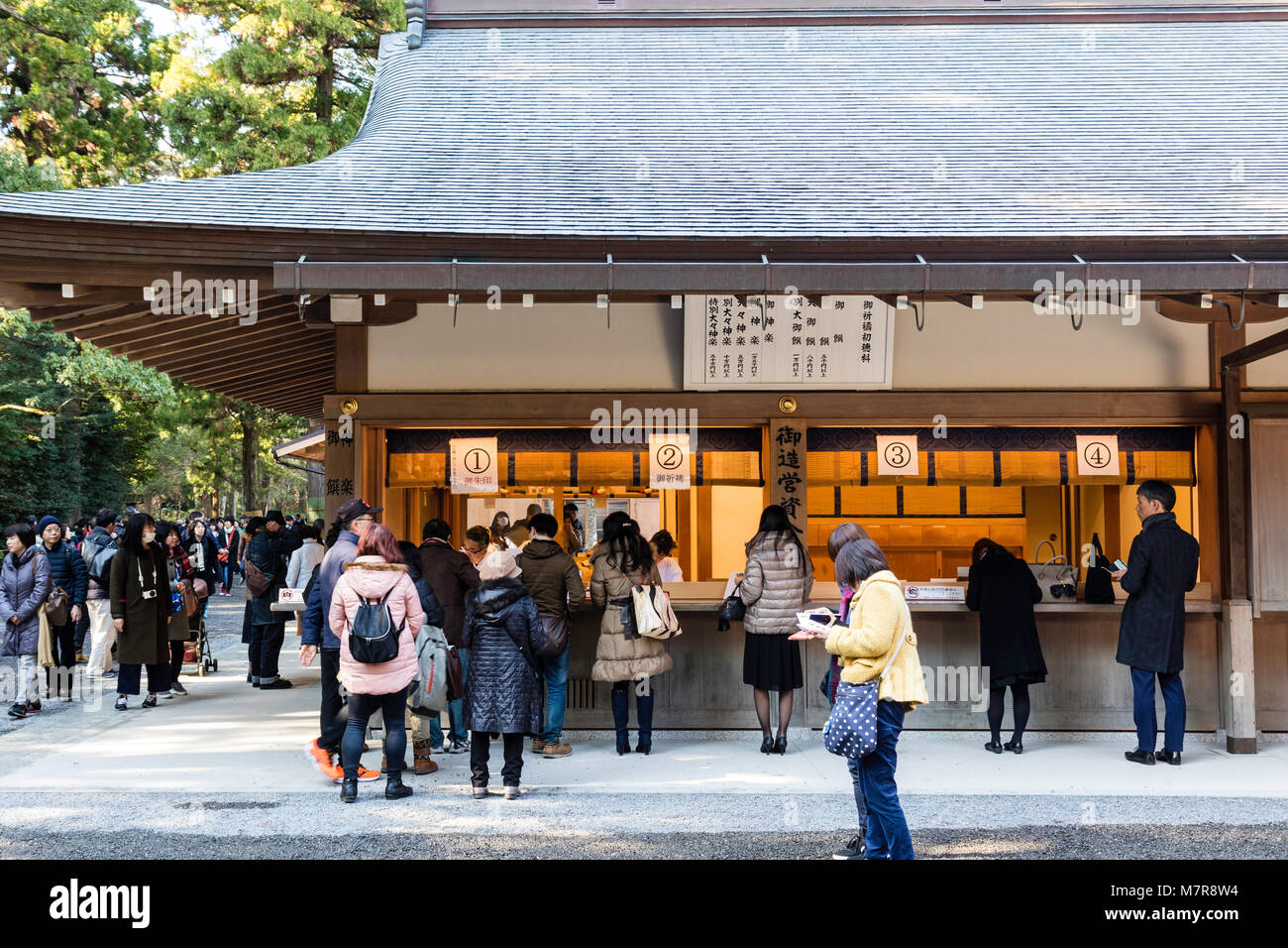 Japan, Ise, Ise-jingu Geku, Outer Shrine. People buying good luck charms from wooden shrine office. - Stock Image