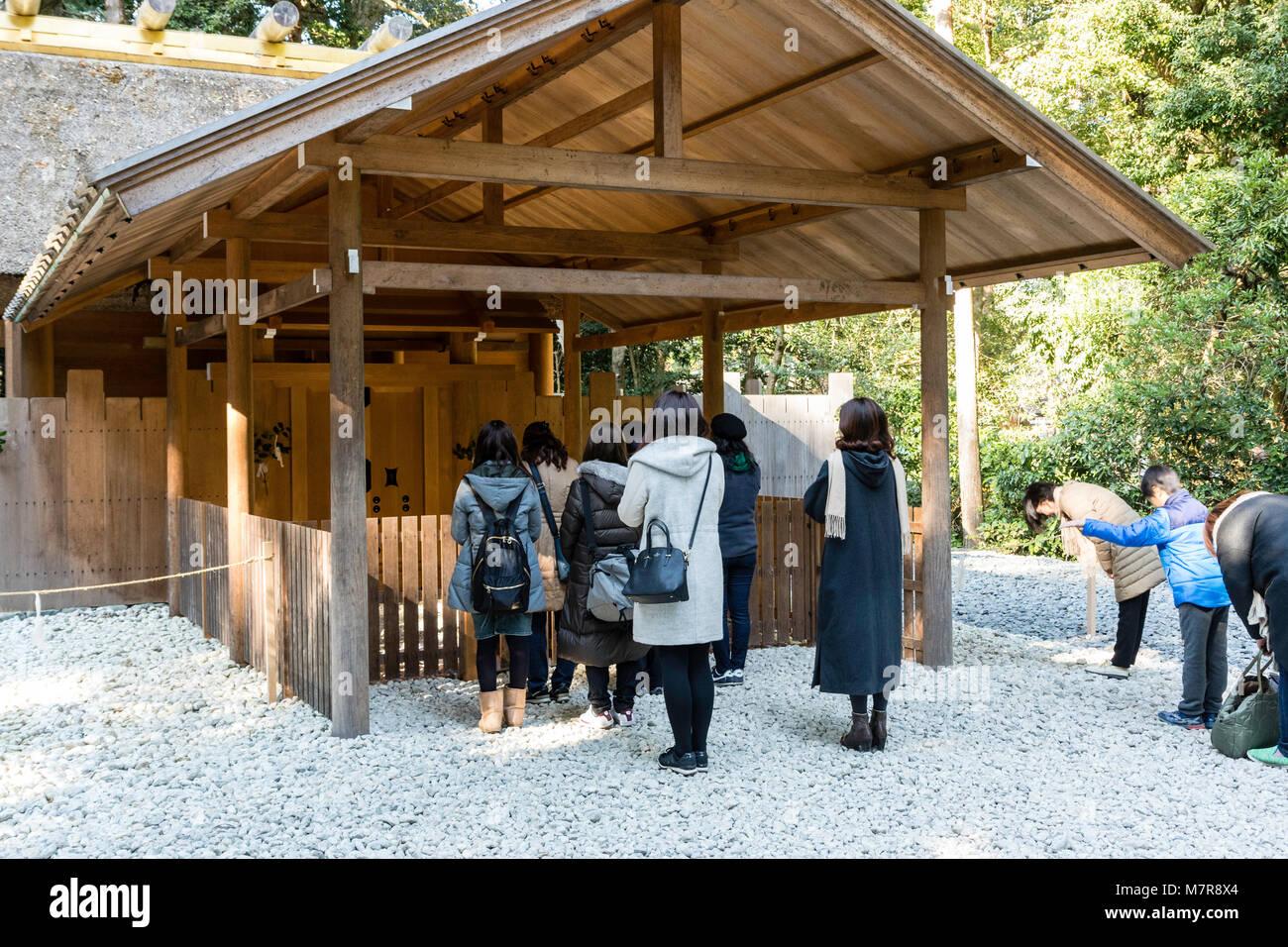 Japan, Ise, Ise-jingu Geku, Outer Shrine. People praying at small wooden shinden shrine building. Shinmei zukuri. - Stock Image