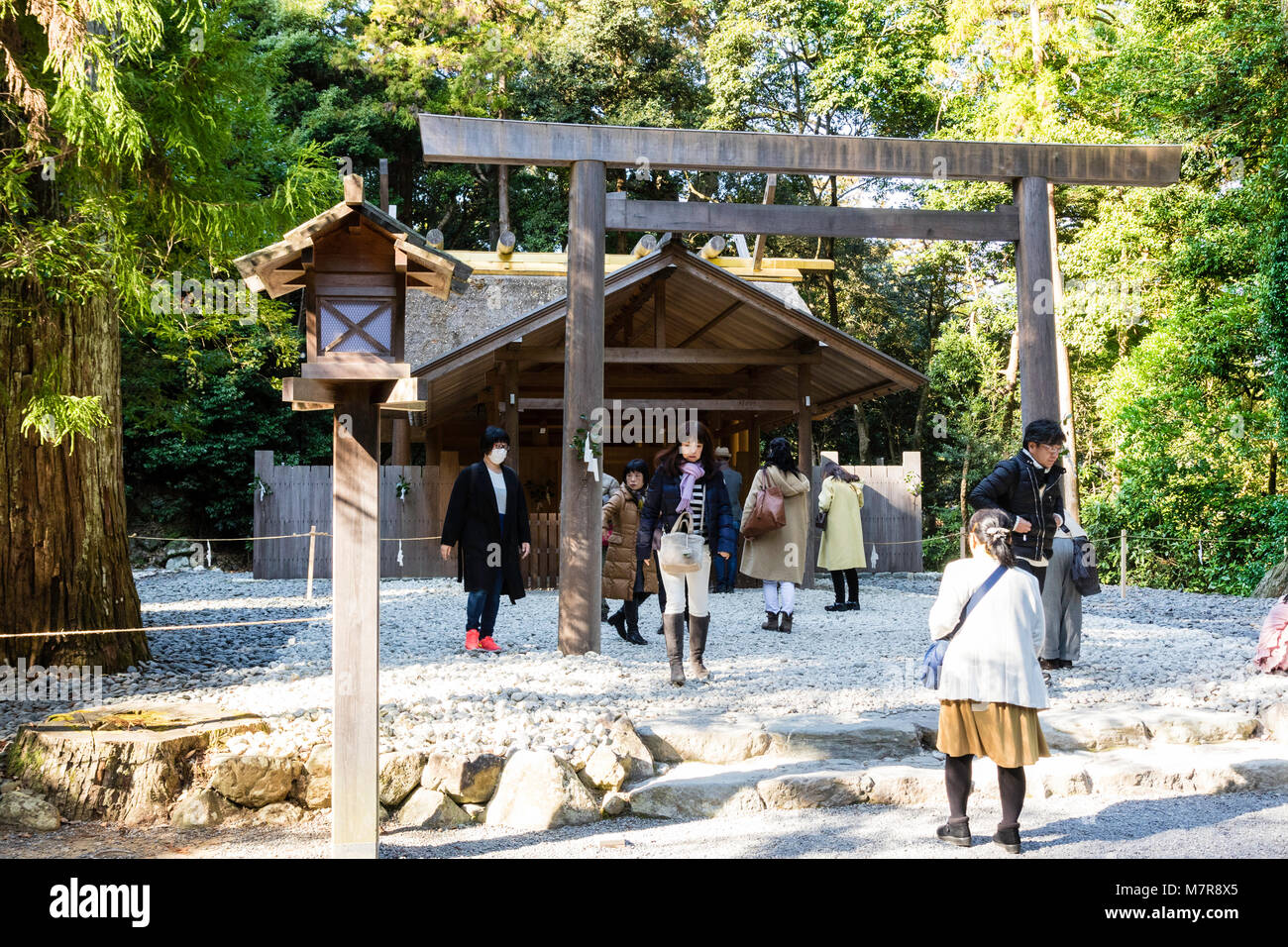 Japan, Ise, Ise-jingu Geku, Outer Shrine. People praying at small wooden shrine with torii gate. - Stock Image