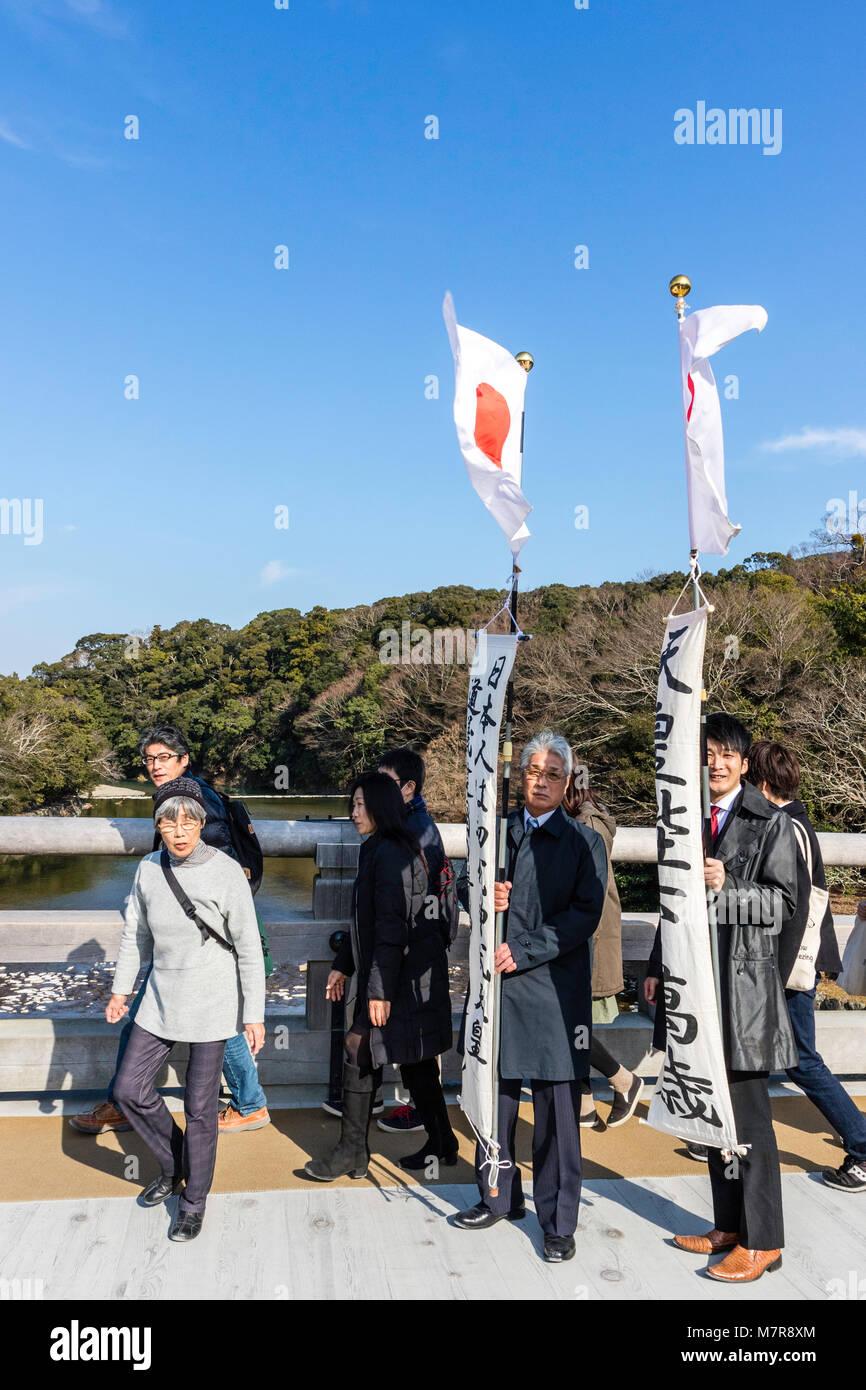 Japan, Ise Grand Shrine, Naiku, inner shrine. Moden day pilgrams on bridge carrying Japanese flag banners. - Stock Image