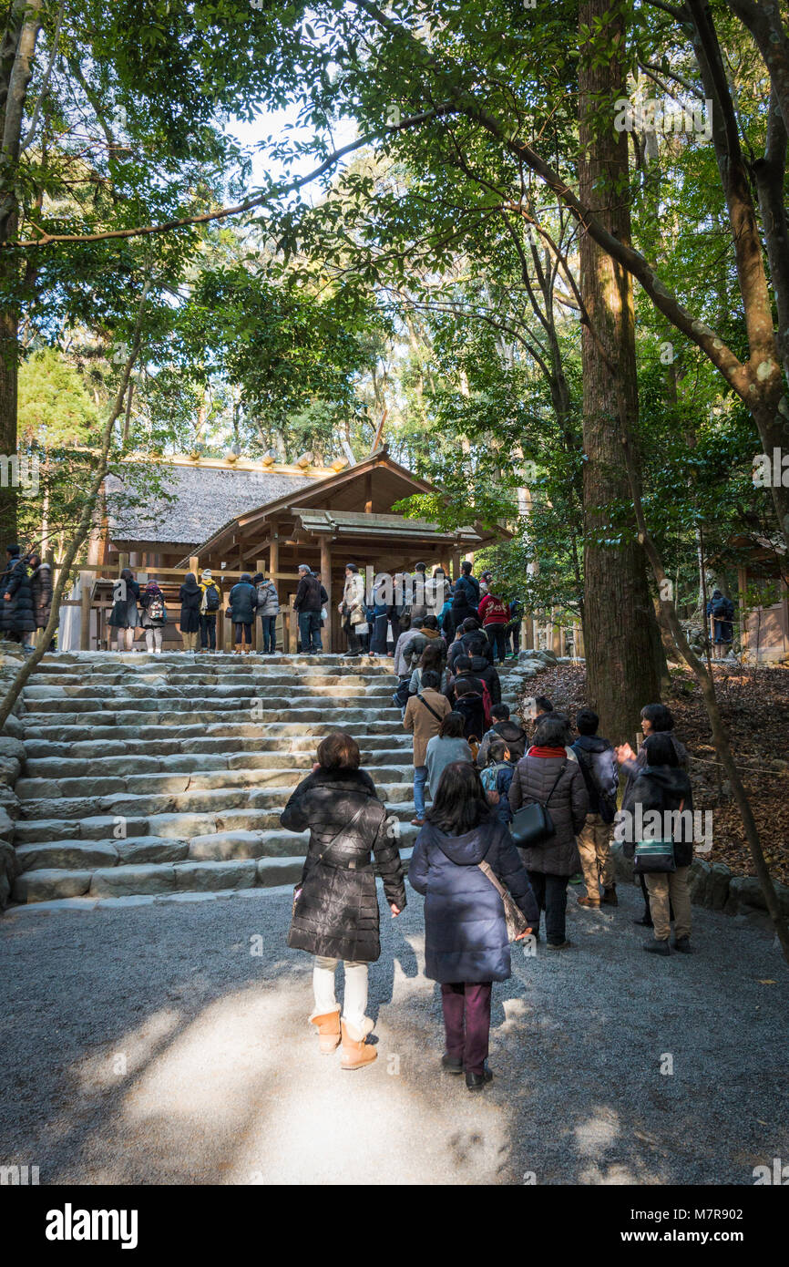 Japan, Ise Grand Shrine, Naiku, inner shrine. People queuing on steps waiting for their turn to pray at small wooden - Stock Image