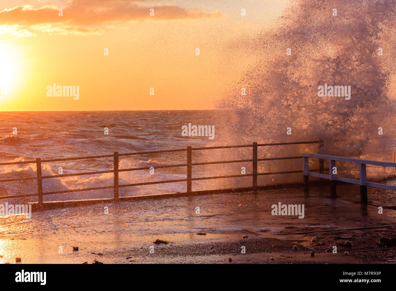 England, Broadstairs. Waves crashing over harbour wall during sunrise (unseen). Sky orange and the sun flaring into - Stock Image