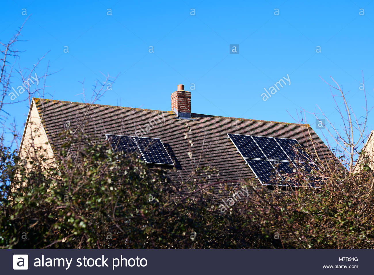 Solar panels on roof of house in Stonesfield in Oxfordshire in the Cotswolds - Stock Image