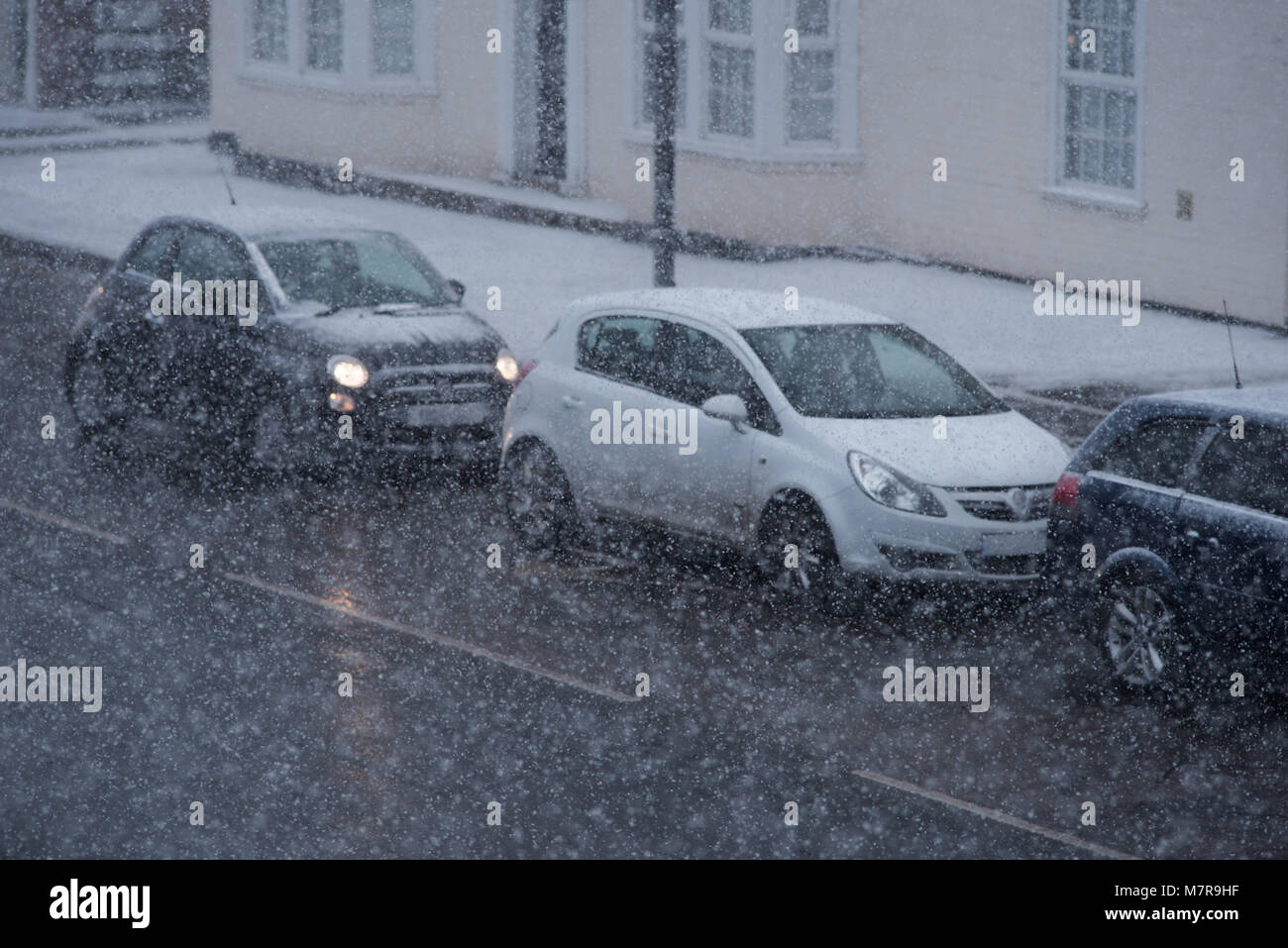 traffic chaos in UK with cars travelling along snow covered road during blizzard conditions - Stock Image