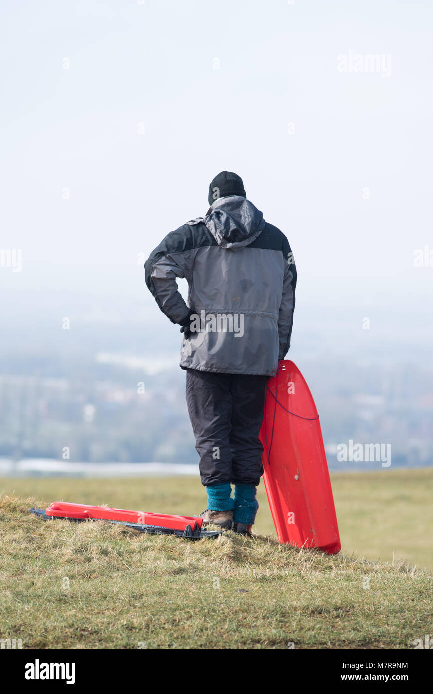 man and woman stand on top of grassy hill admiring distant view with bright red plastic sledge - Stock Image