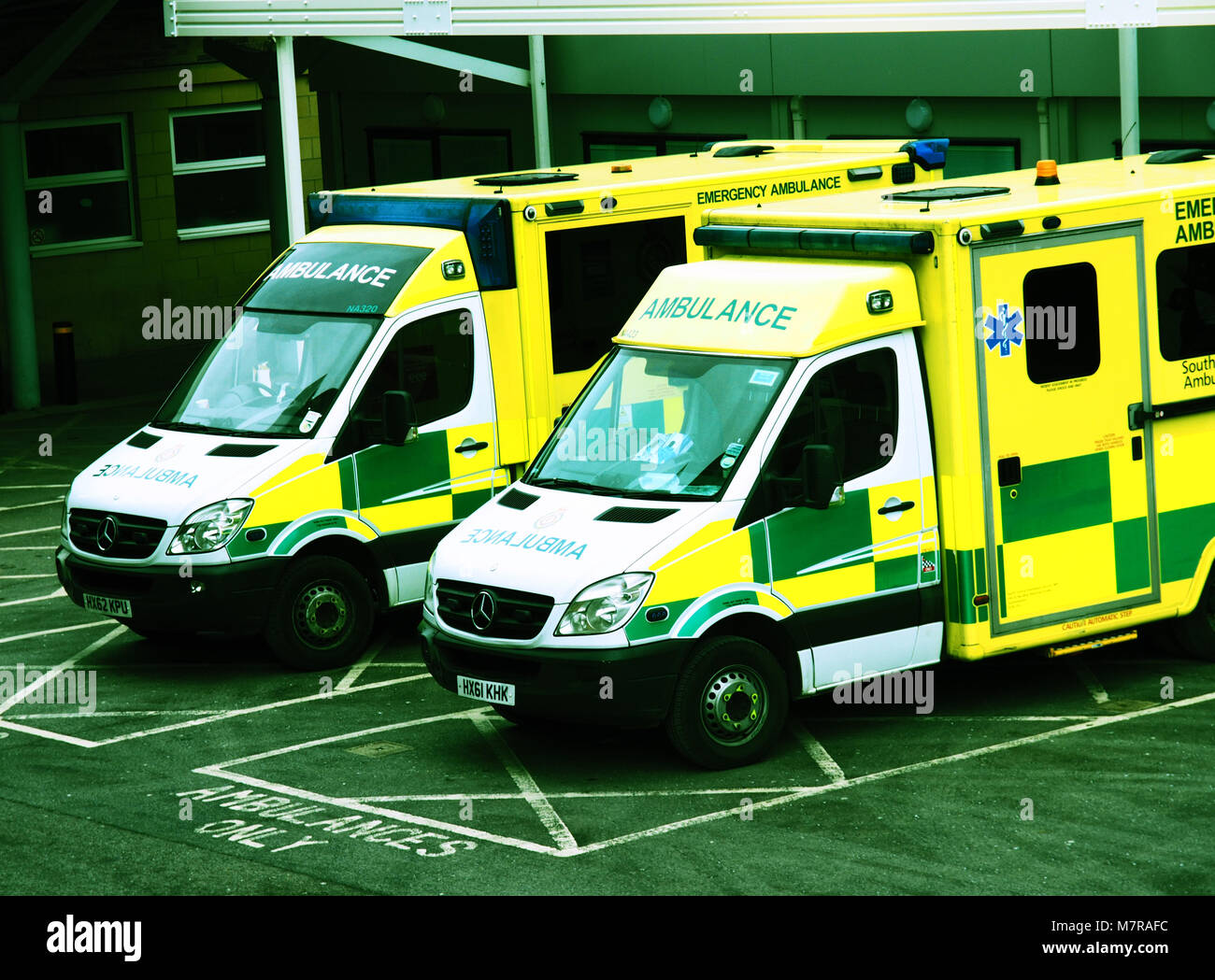 Two ambulances waiting outside an A&E department of a hospital in a cross-processed effect - Stock Image