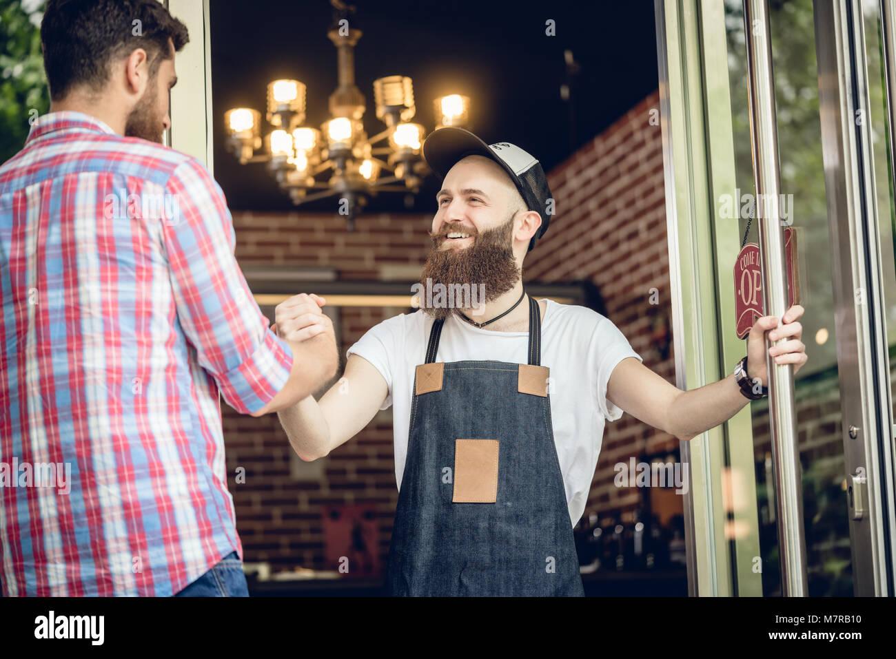 Cheerful barber greeting his male customer - Stock Image