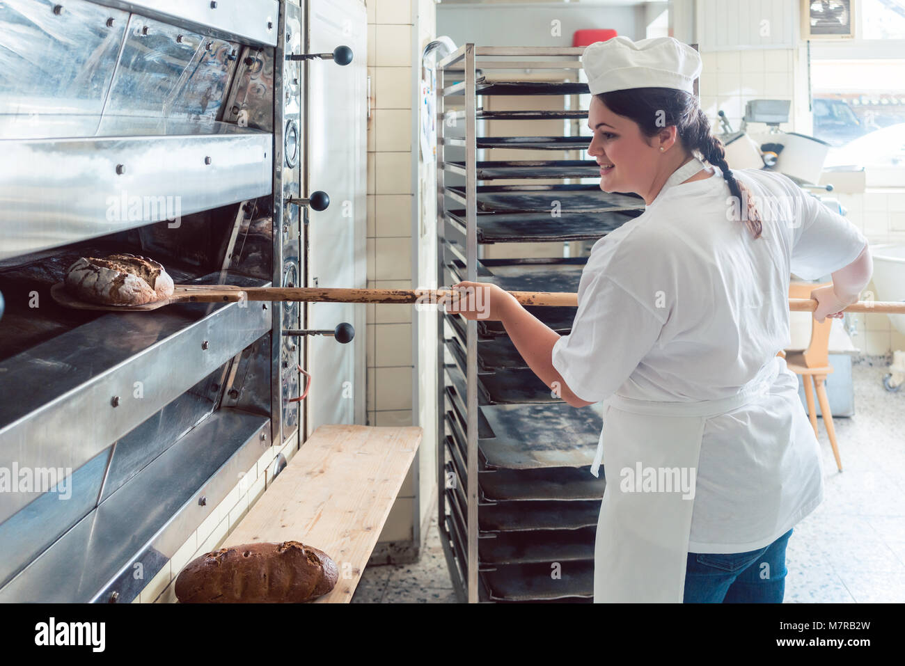 Baker woman getting bread out of bakery oven - Stock Image