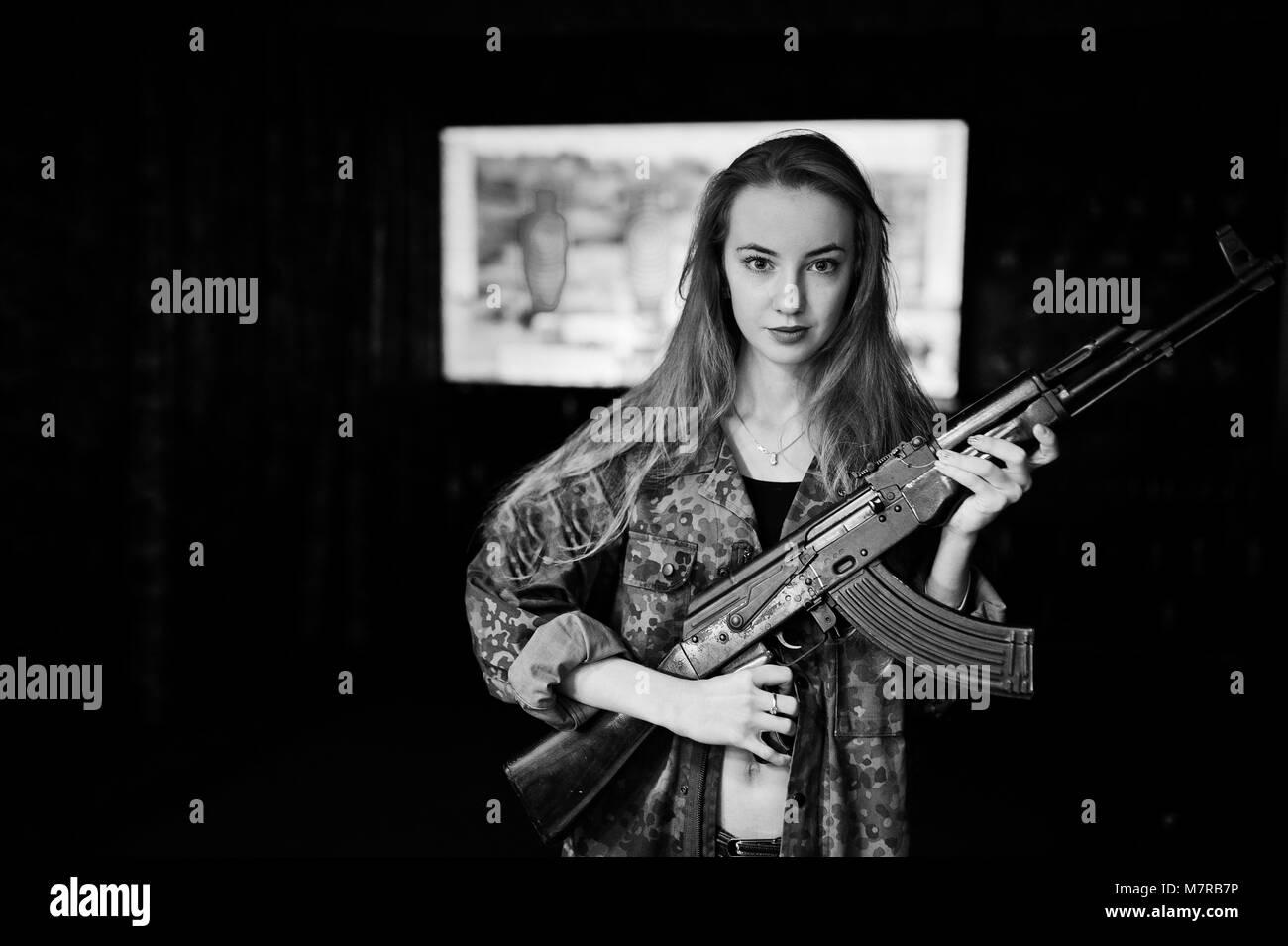 Girl with machine gun at hands on shooting range. - Stock Image