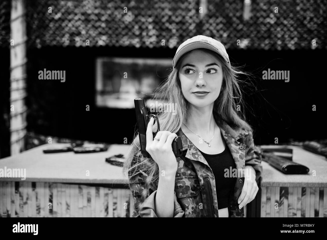 Military girl in camouflage uniform with gun at hand against army background on shooting range. - Stock Image