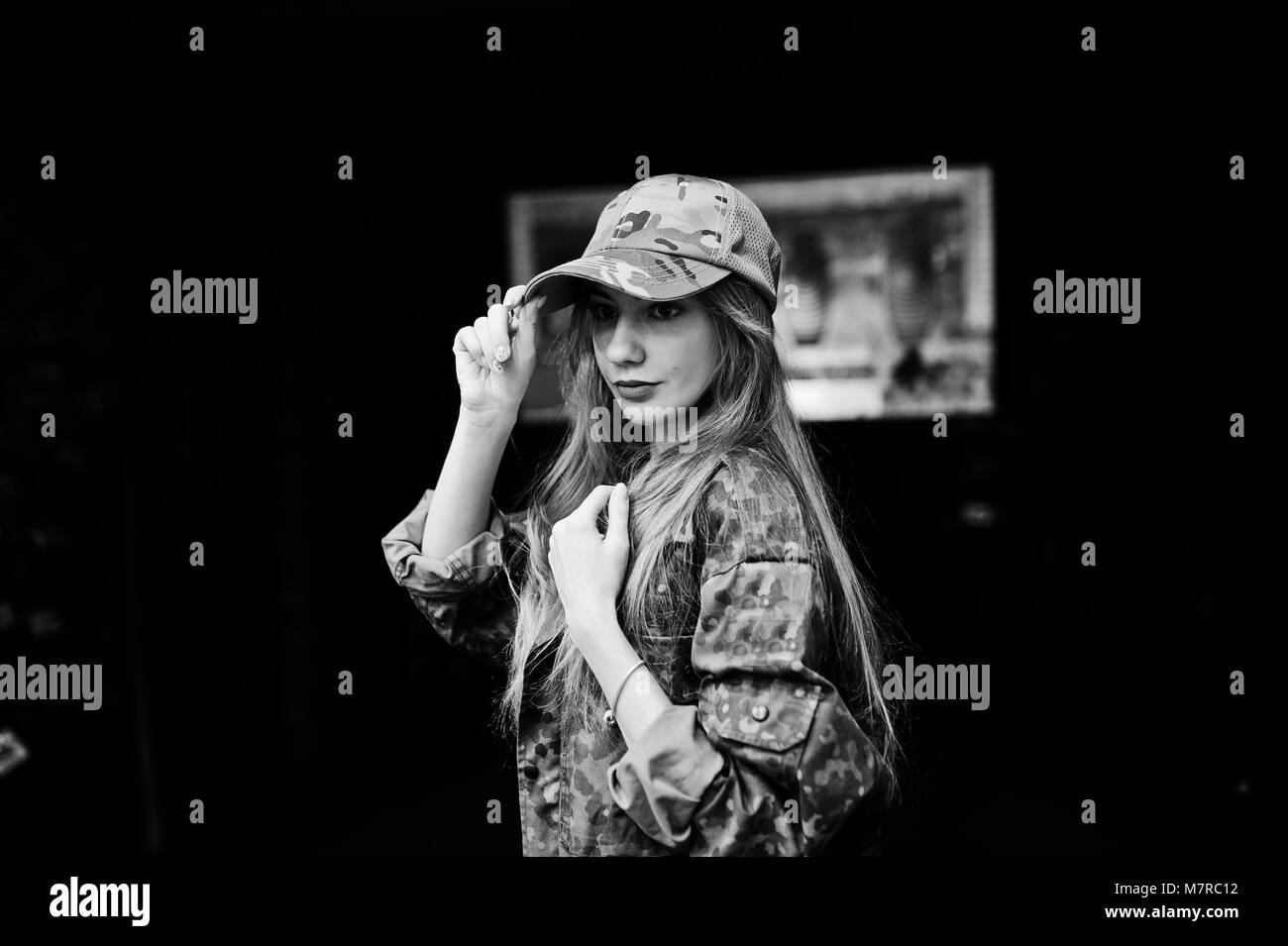 Military girl in camouflage uniform against army background on shooting range. - Stock Image