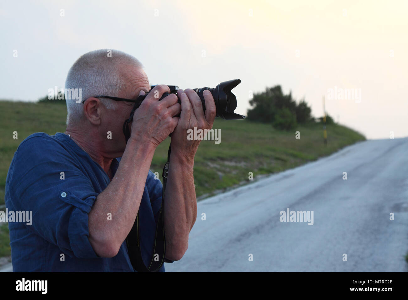 White man in the 60's photographed in profile. The man is photographing. -  Stock