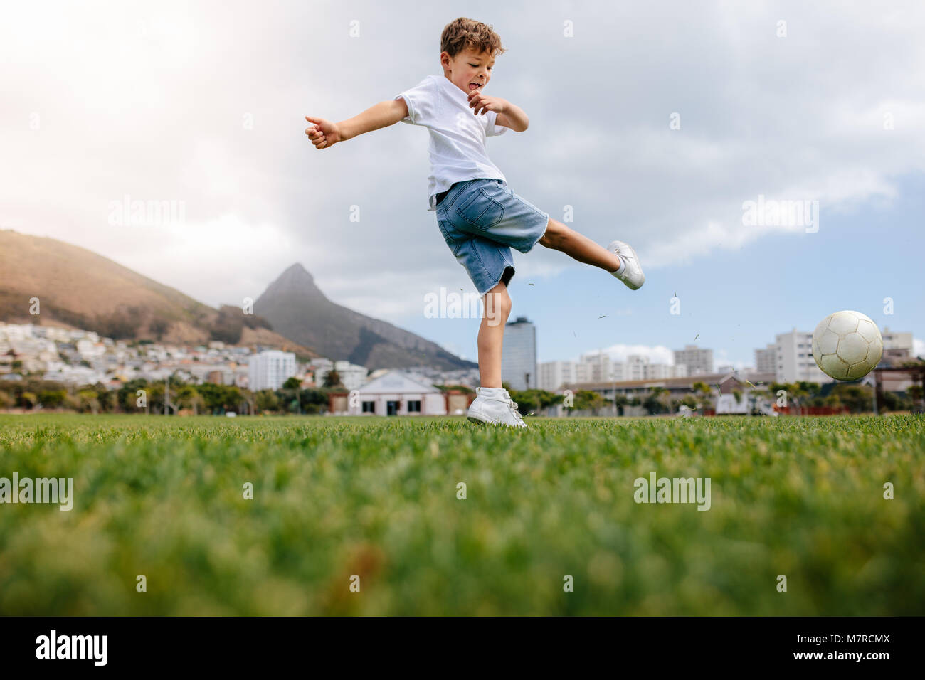 Boy kicking a football in a playground. Low angle view of a boy playing football in a playfield. - Stock Image