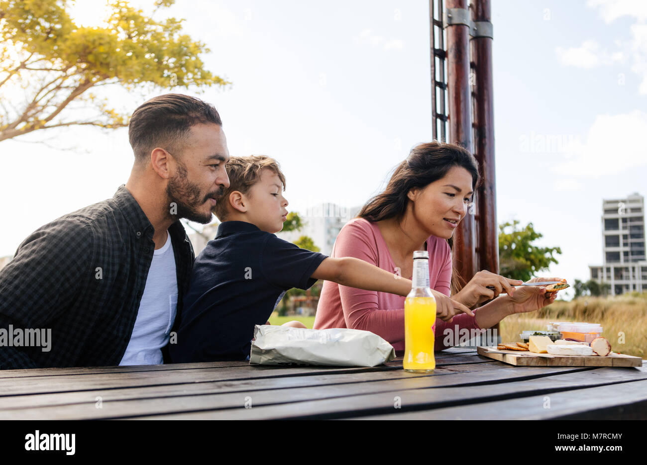 Couple with their child on a day out. Woman preparing snacks outdoors for her family. - Stock Image