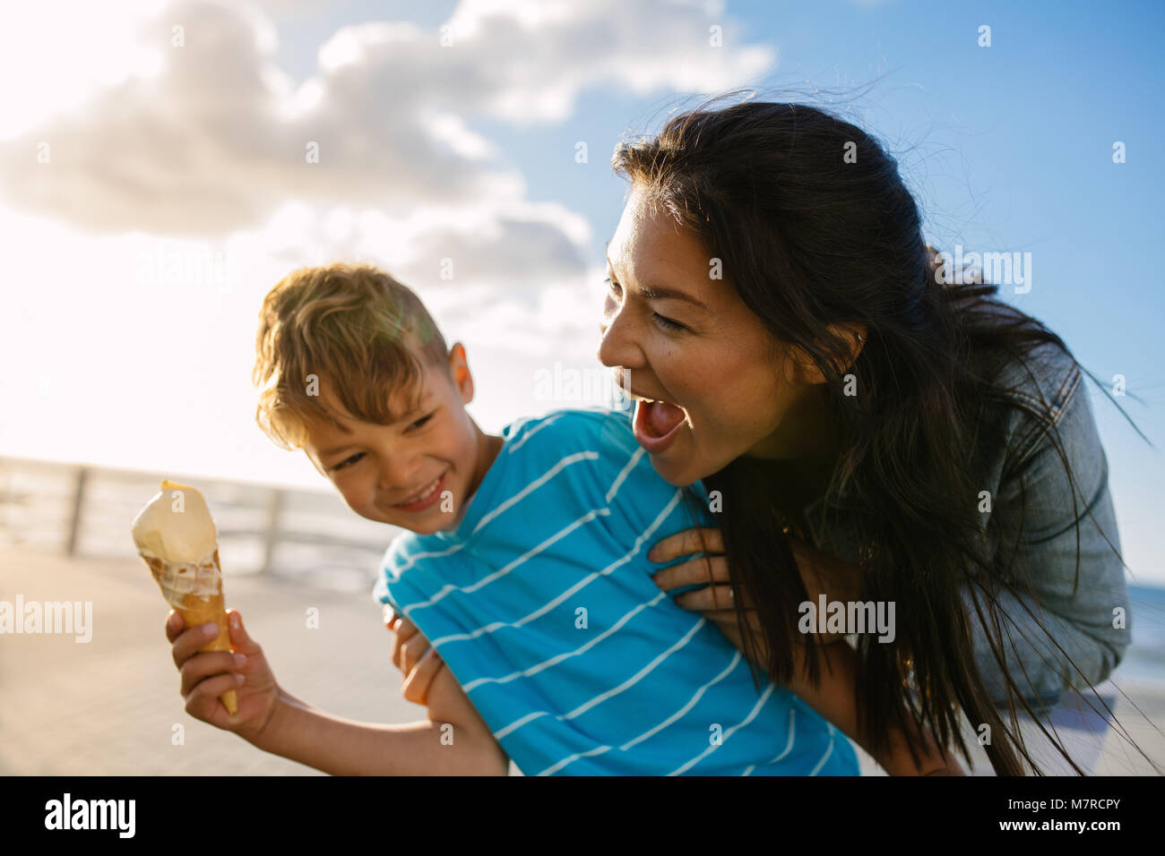 Boy eating an ice cream standing near seafront with his mother. Little boy holding an ice cream cone while his mother - Stock Image