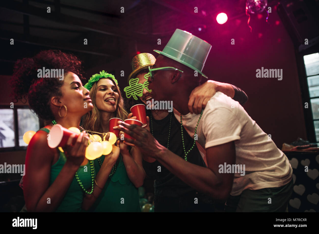 Group of cheerful friends having fun at bar. Multi-ethnic men and women partying and dancing at night club. Celebrating - Stock Image