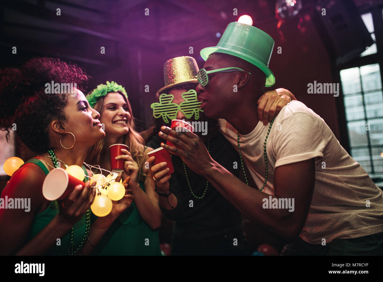 Multi-ethnic men and women having fun at the bar. Group of friends celebrating St. Patrick's Day at nightclub. - Stock Image