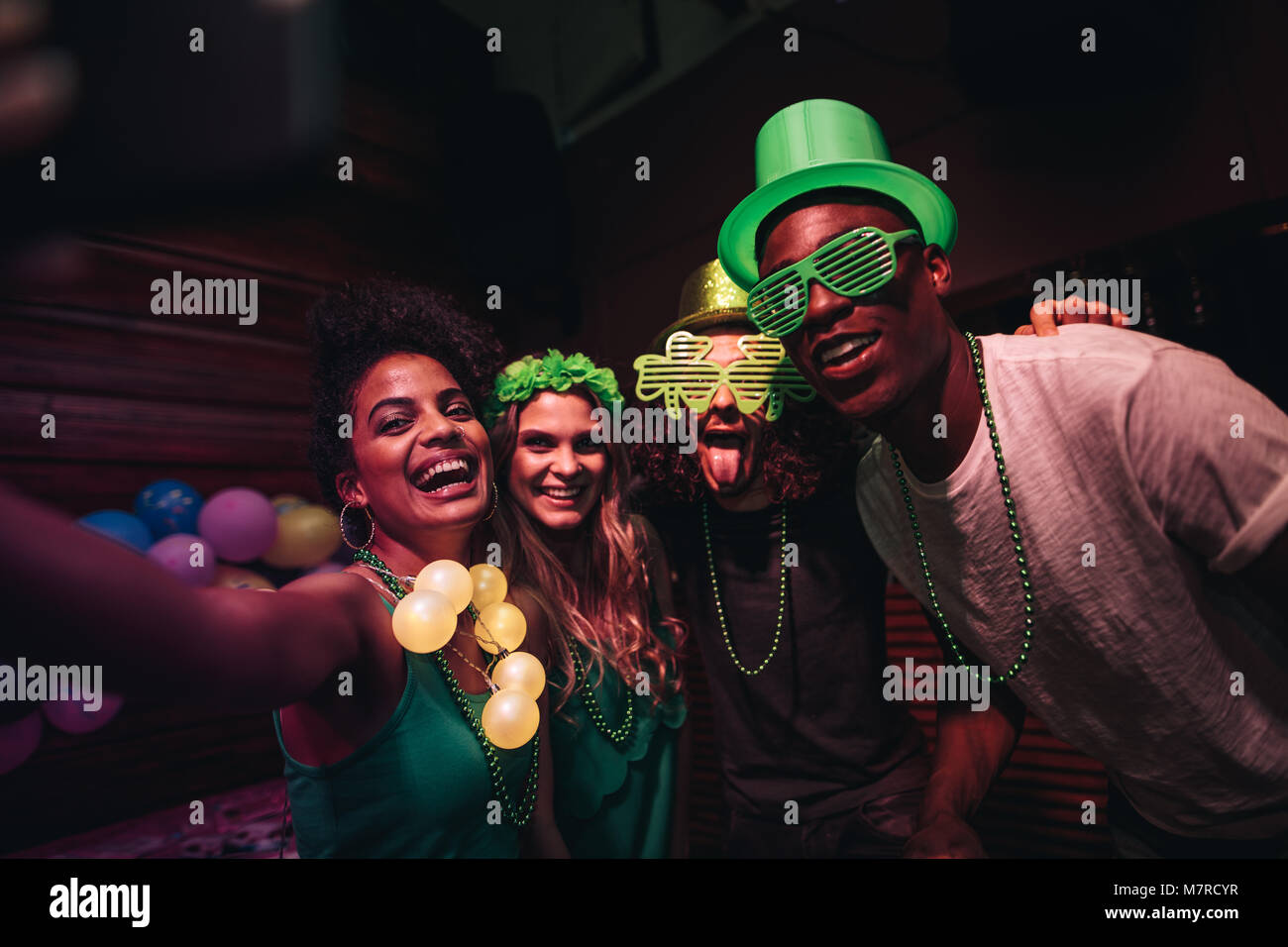 Group of friends enjoying at party in the bar and taking selfie with smart phone. Cheerful en and women partying - Stock Image