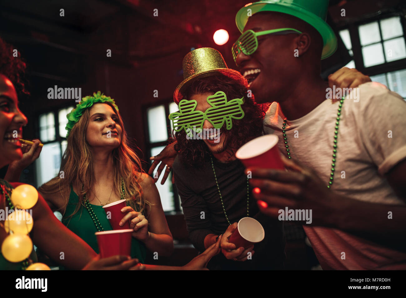 Group of young men and woman celebrating St. Patrick's Day. Friends having fun at the bar with green party glasses - Stock Image