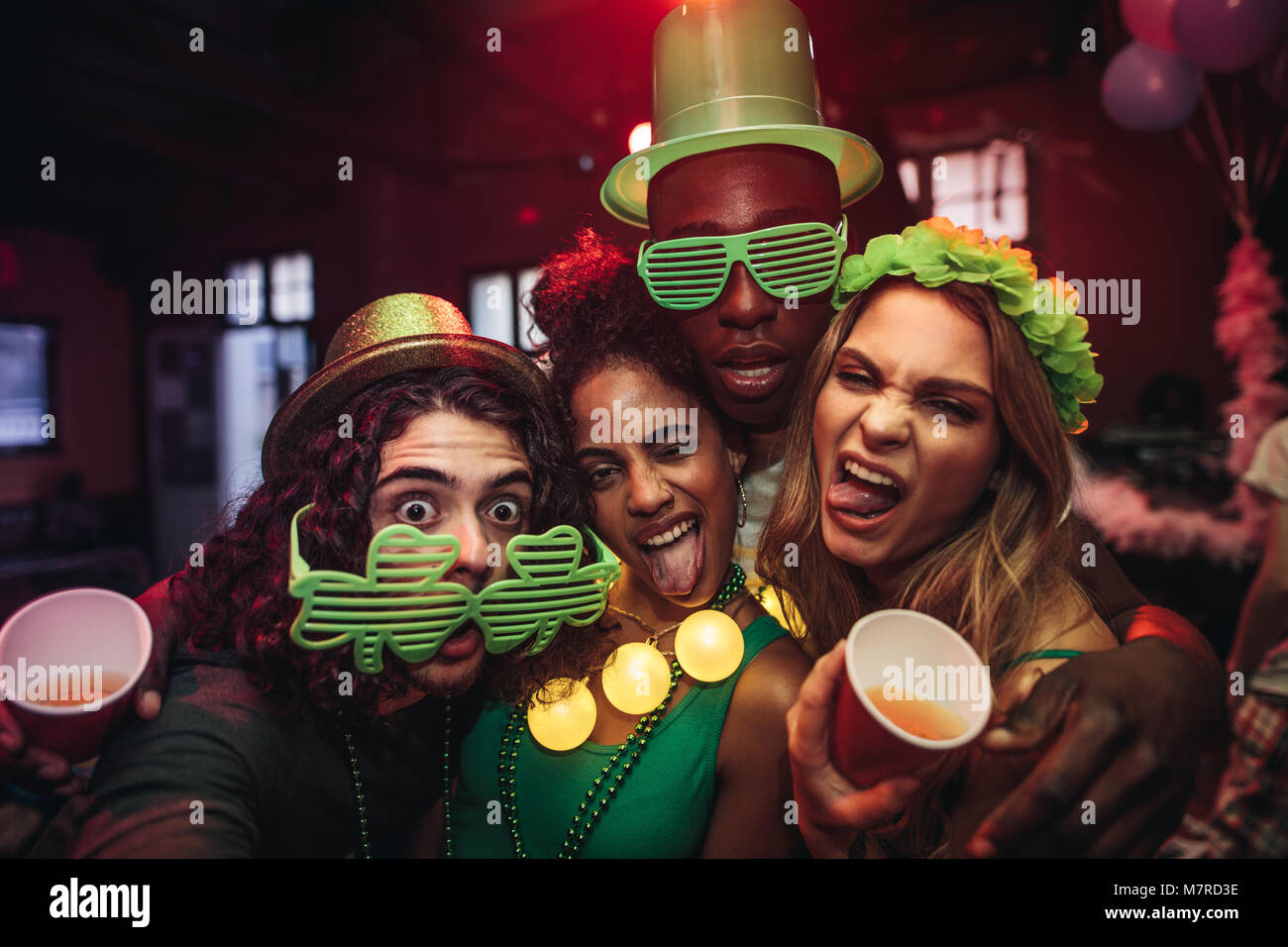 Crazy young friends enjoying a party at pub. Men and women in green clover party glasses and leprechaun hat at night - Stock Image