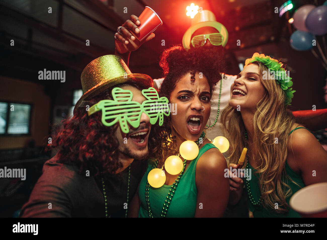 Group of young friends celebrating St. Patrick's Day at bar. People having fun at the bar. - Stock Image