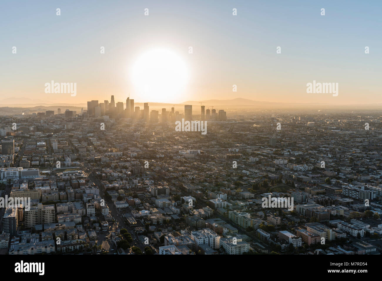 Aerial view of sunrise behind streets and buildings in the urban core of Los Angeles California. - Stock Image