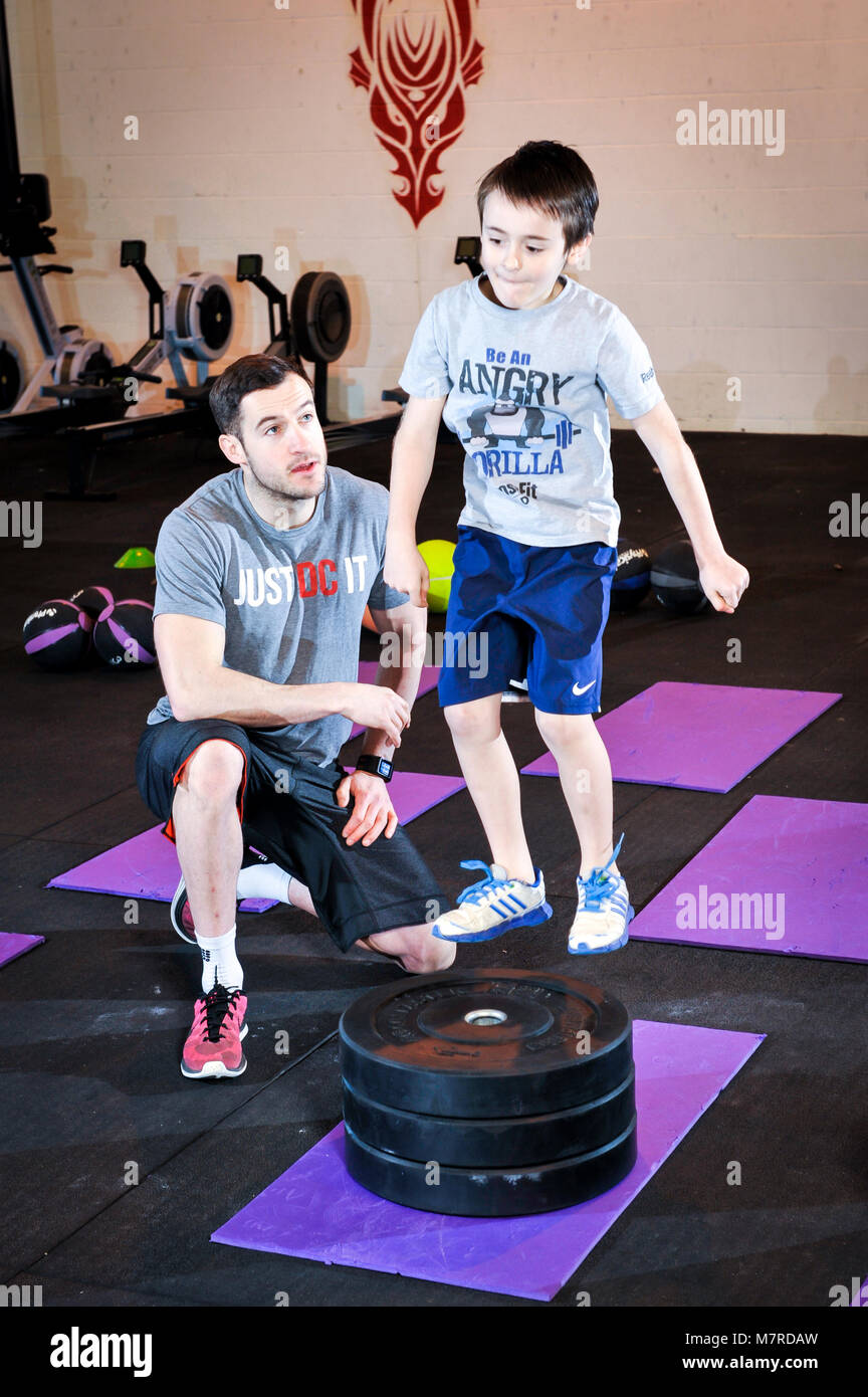 Young boy jumping on and off a platform during a keep fit gym session with an instructor - Stock Image