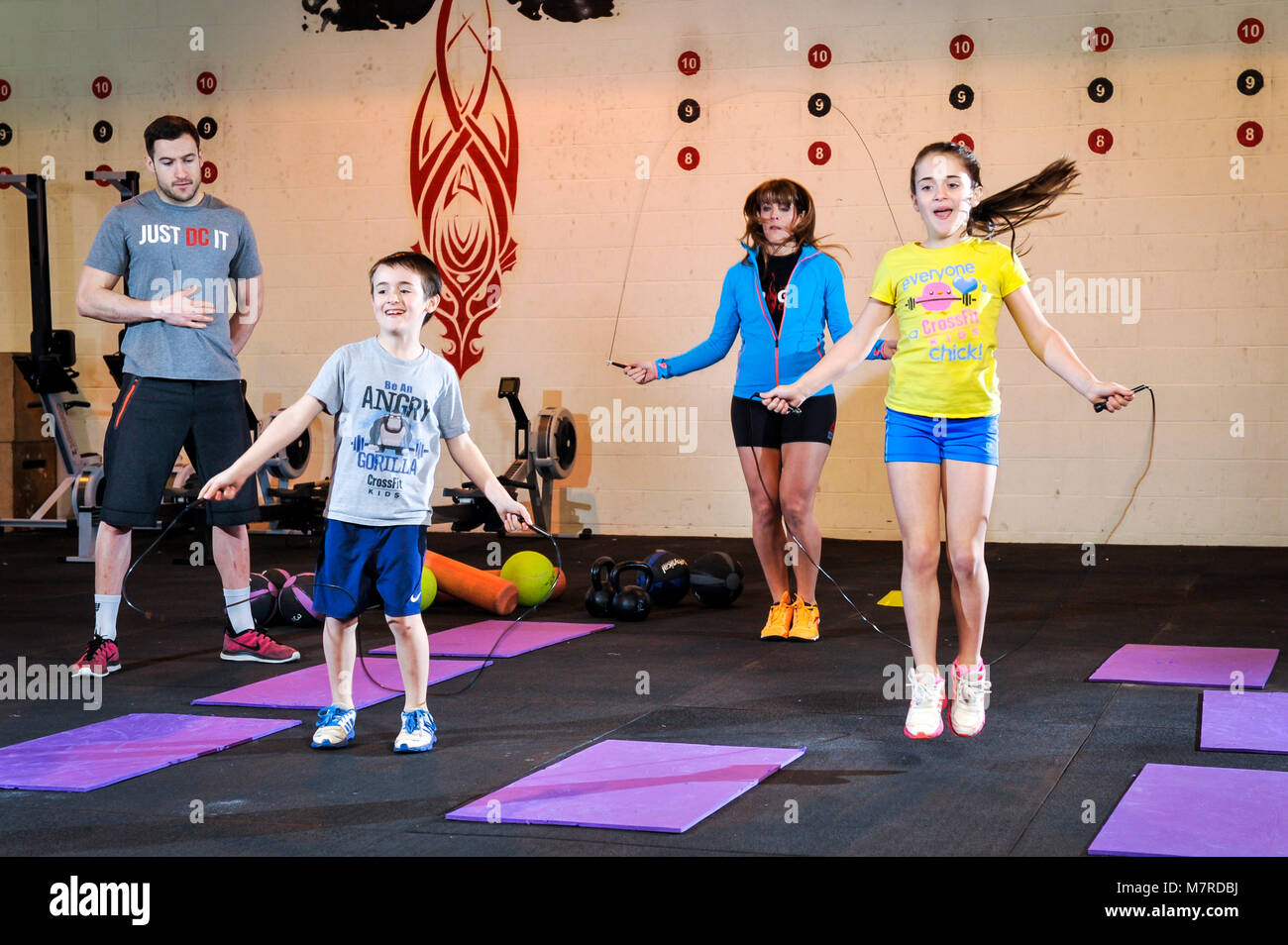 A mother and her two children are skipping during an exercise class in a gym with a gym instructor. - Stock Image