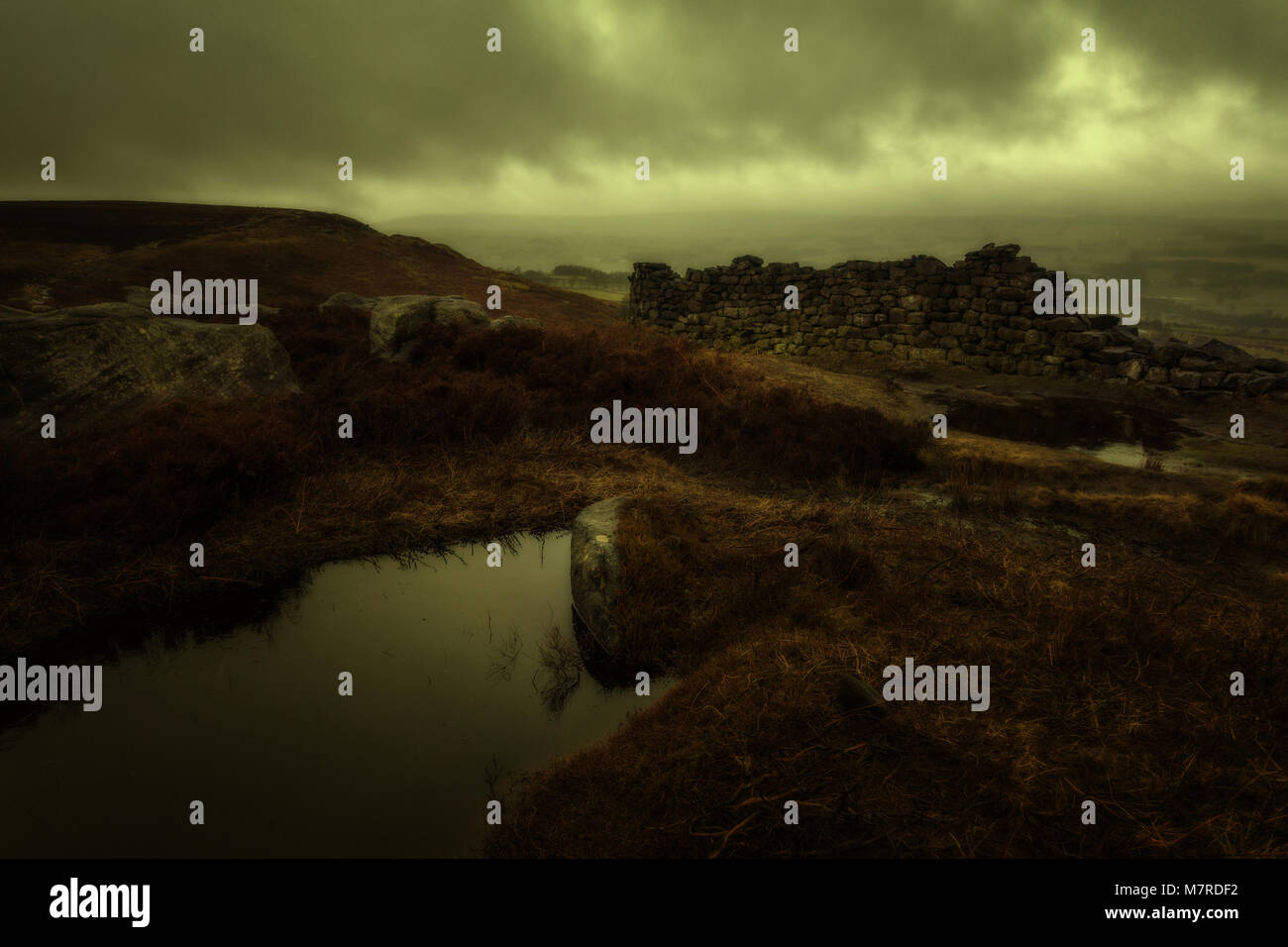 Moody and atmospheric scene of a damp moorland day with stone wall - Stock Image