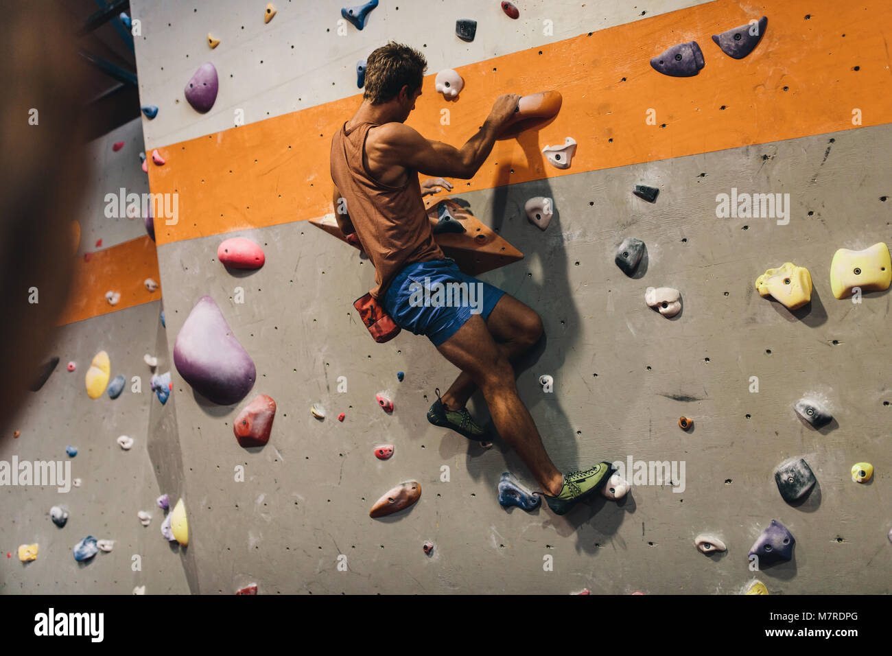 Man bouldering at an indoor climbing centre. Climber practicing rock climbing at an indoor climbing gym. - Stock Image