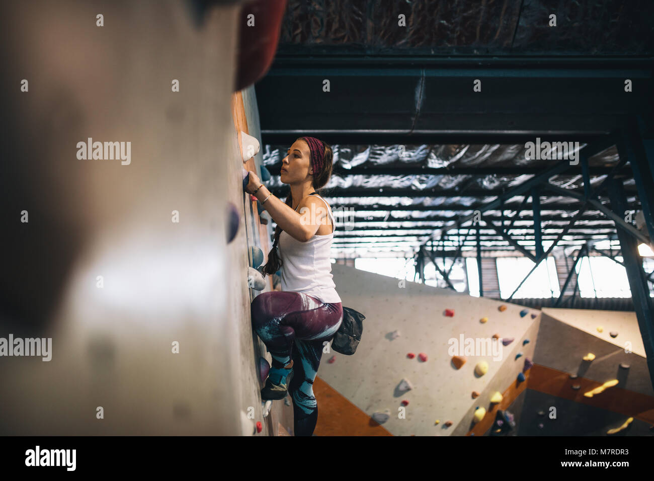 Woman bouldering at an indoor climbing centre. Climber practicing rock climbing at an indoor climbing gym. - Stock Image