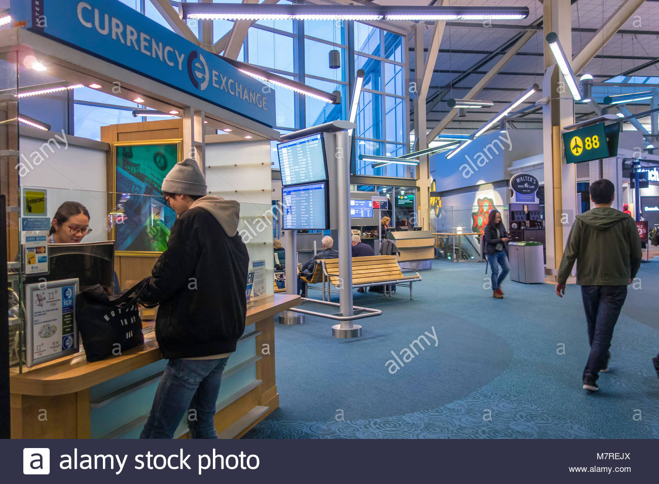 Traveler exchanging currency at a currency exchange in Vancouver International Airport YVR British Columbia Canada - Stock Image