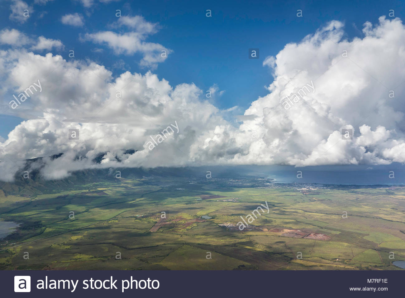 Warm moist air rising over mountainous Maui create cumulonimbus clouds watering sugar cane a hydrologic cycle state - Stock Image
