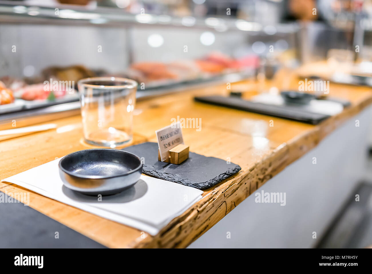 Japanese restaurant sign in traditional style interior asian sushi wooden bar counter menu bowl glass napkin setting empty nobody closeup & Japanese restaurant sign in traditional style interior asian sushi ...