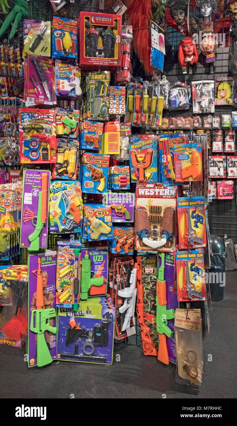 Plastic gund, rifles and other weapons for sale at the Halloween Adventure, a costume shop in Greenwich Village, - Stock Image