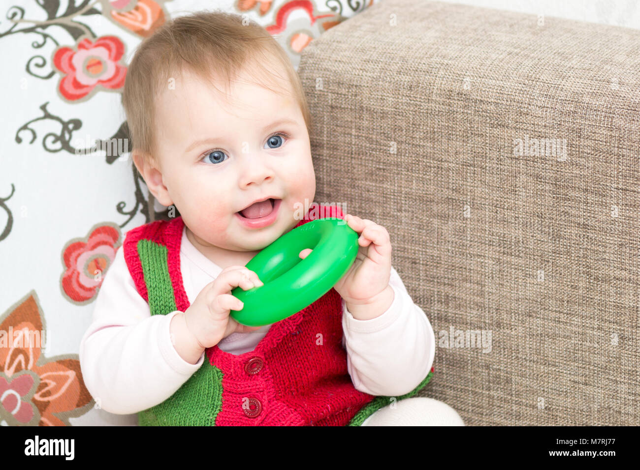 8 months old baby girl playing with pyramid ring - Stock Image