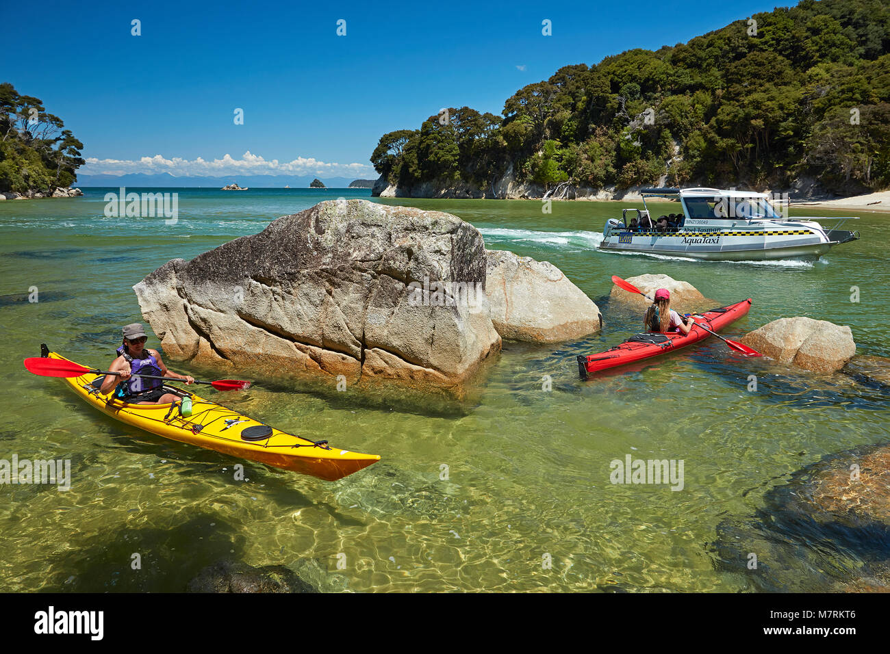 Kayakers and water taxi, Mosquito Bay, Abel Tasman National Park, Nelson Region, South Island, New Zealand (model - Stock Image