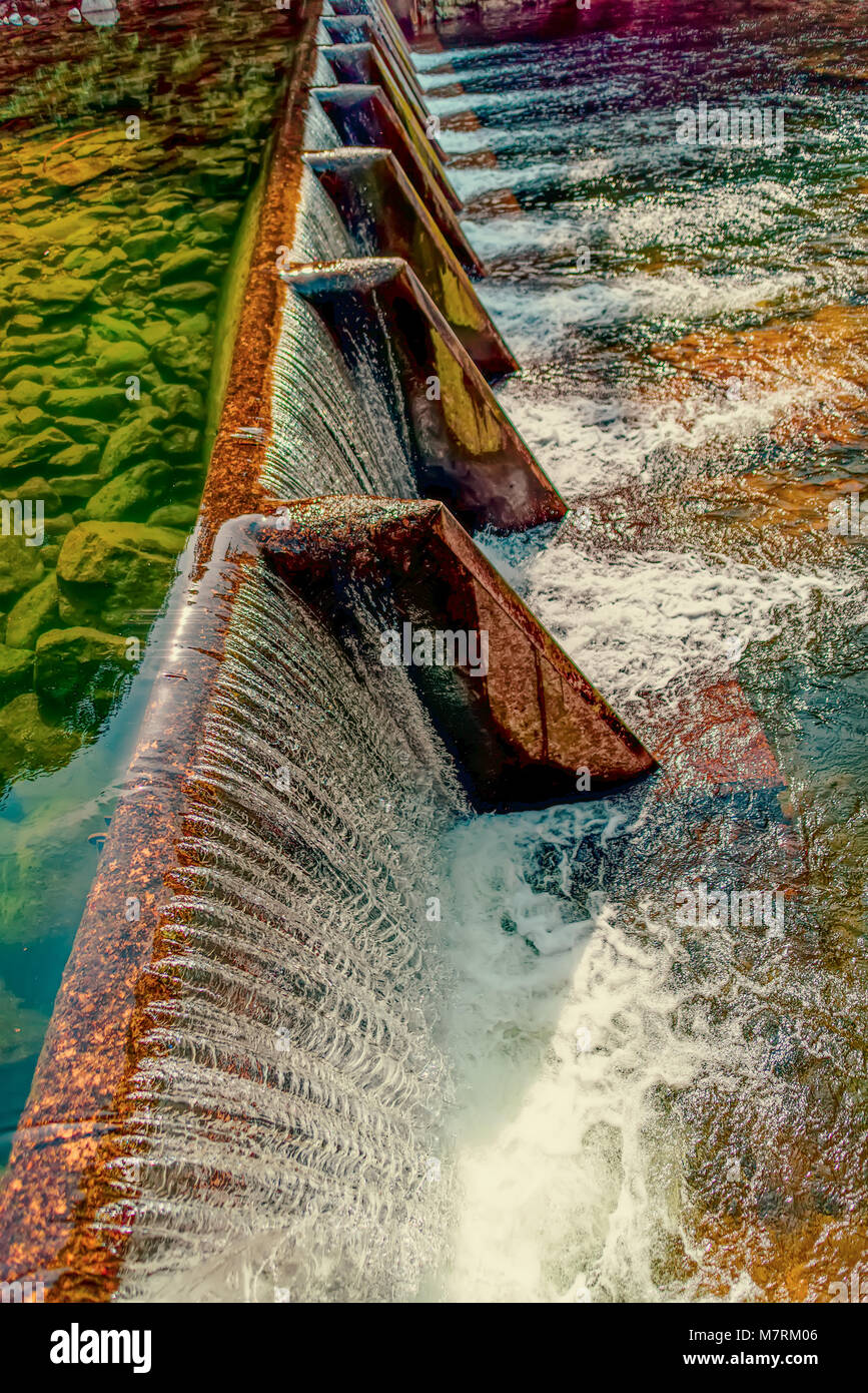 an artificial waterfall of water flows from the concrete dam of the reservoir, calm, clear water and stones at the - Stock Image