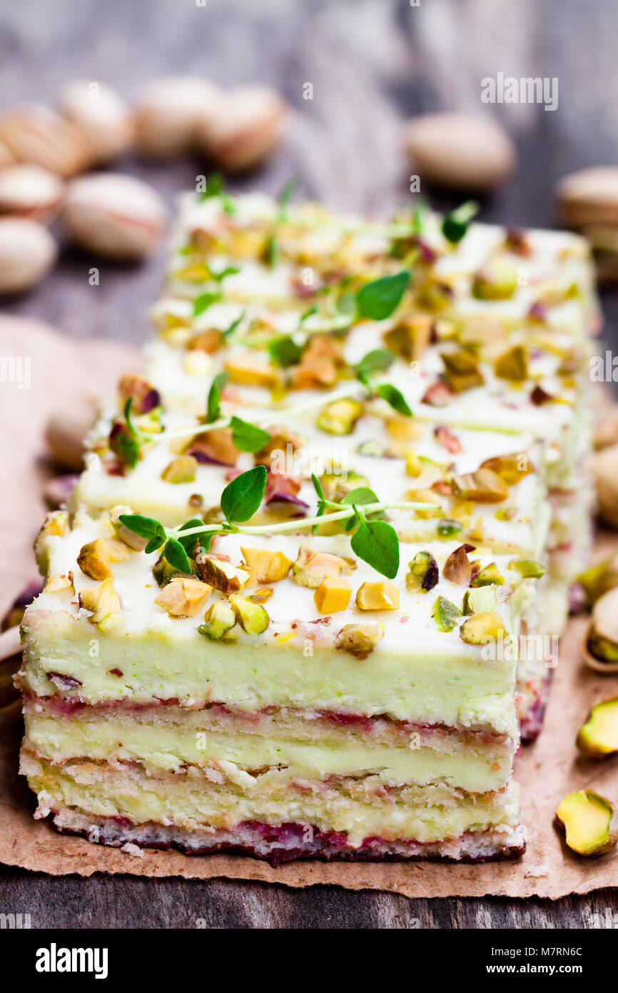 Slices  of layered cake with pistachio on wooden background - Stock Image