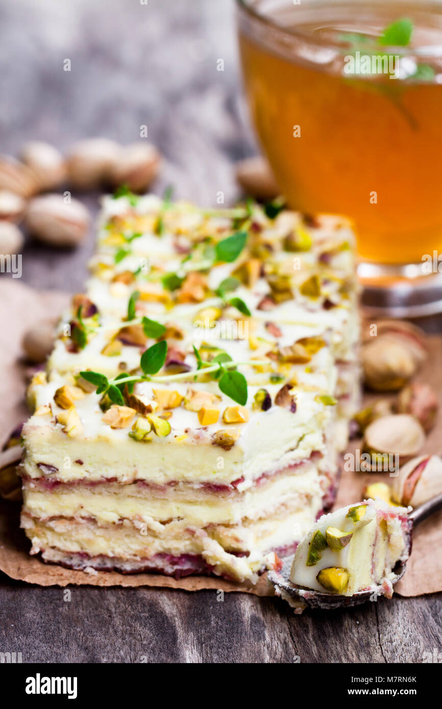 Slices  of layered cake with pistachio and a cup of green herbal tea - Stock Image