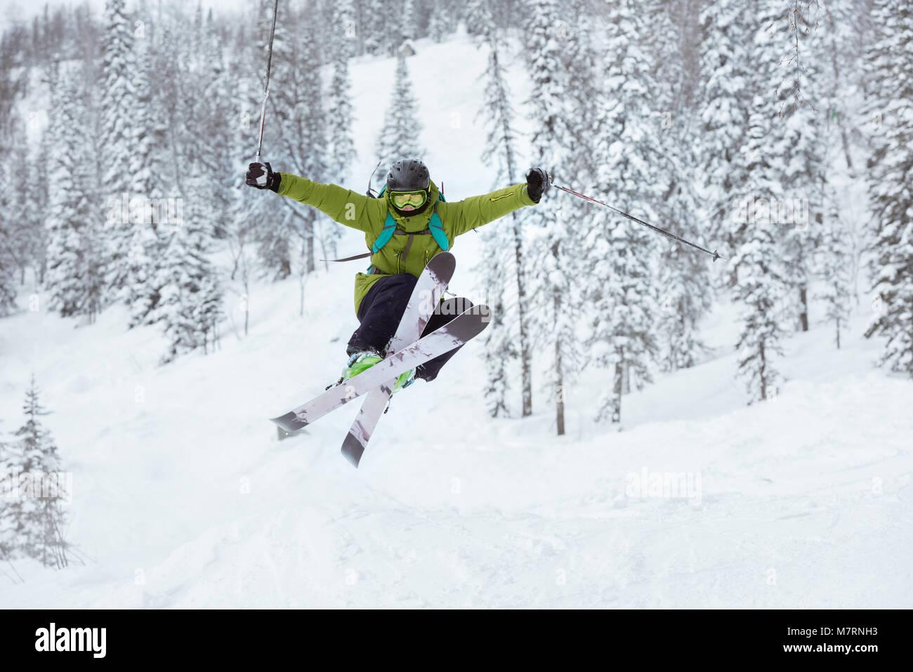 Skier jumps offpiste ski slope resort - Stock Image