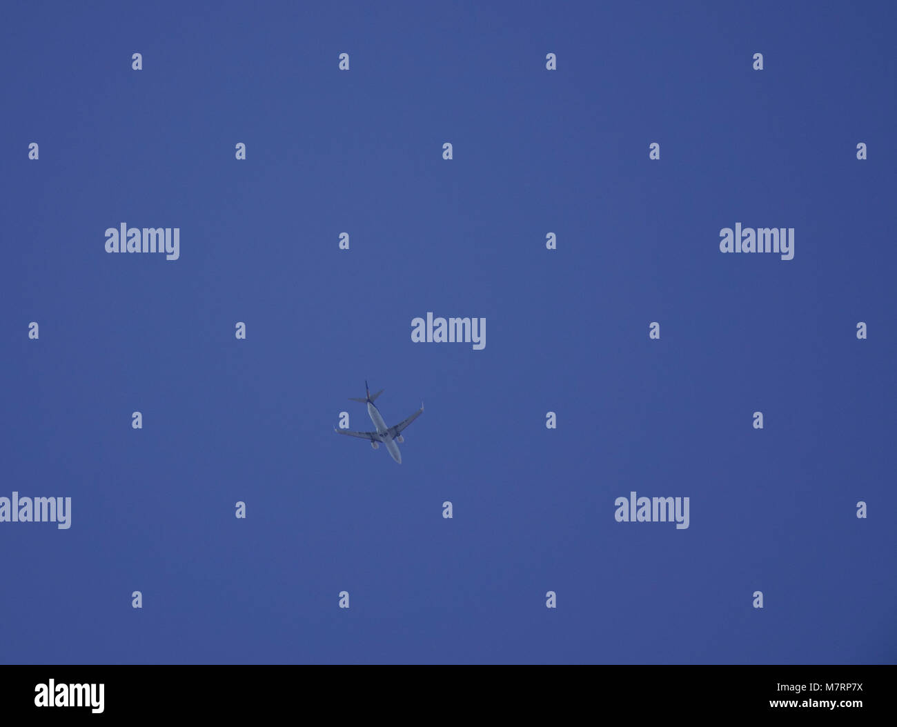A civil aircraft flying in the blue sky at sunny day. - Stock Image