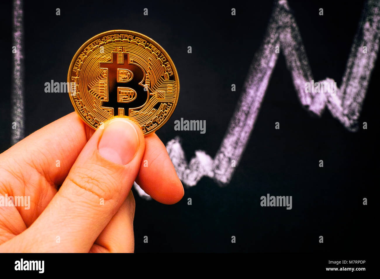 Golden Bitcoin in woman hand against blackboard with chalk drawing graph. Close-up. Stock Photo