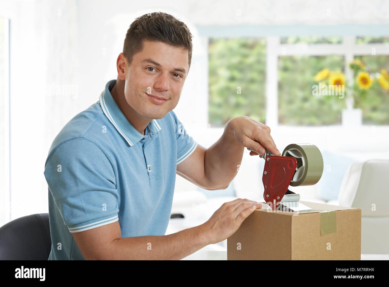Portrait Of Man At Home Sealing Box For Dispatch - Stock Image