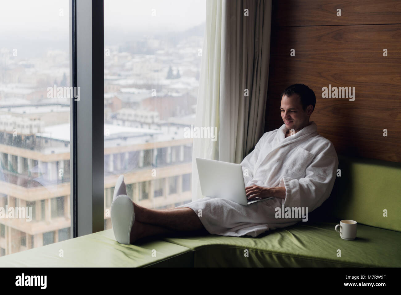 Young smiling businessman working on laptop computer wearing white bath robe sitting near window with cup of coffee - Stock Image