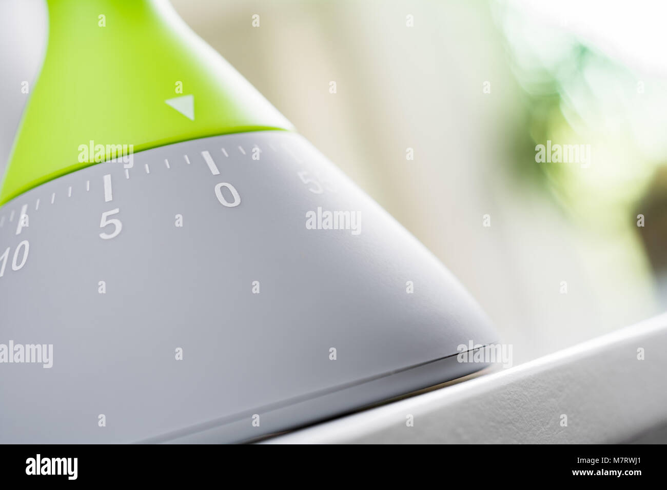 0 Minutes / 1 hour - Closeup Of An Analog Green / Grey Kitchen Egg Timer On White Table - Stock Image