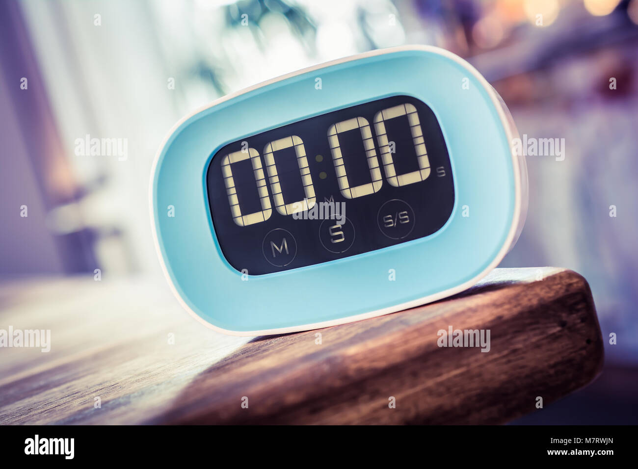 0 Minutes - Closeup Of A Digital Blue Kitchen Timer On Edge Of Wooden Table - Stock Image