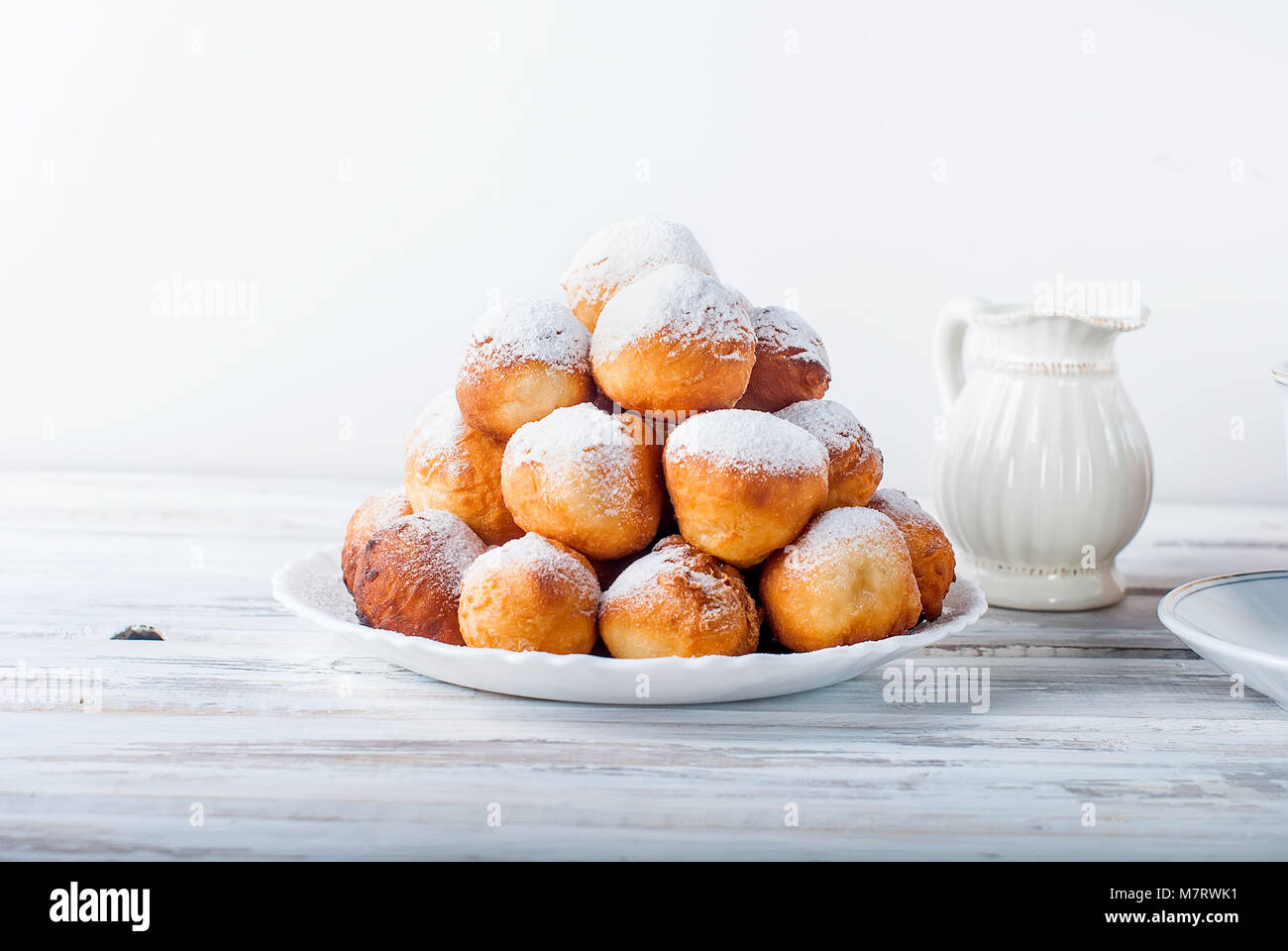 sweet donuts laid out pyramid sprinkled with powdered sugar on the plate , Milk jug and cup, breakfast , copy space Stock Photo