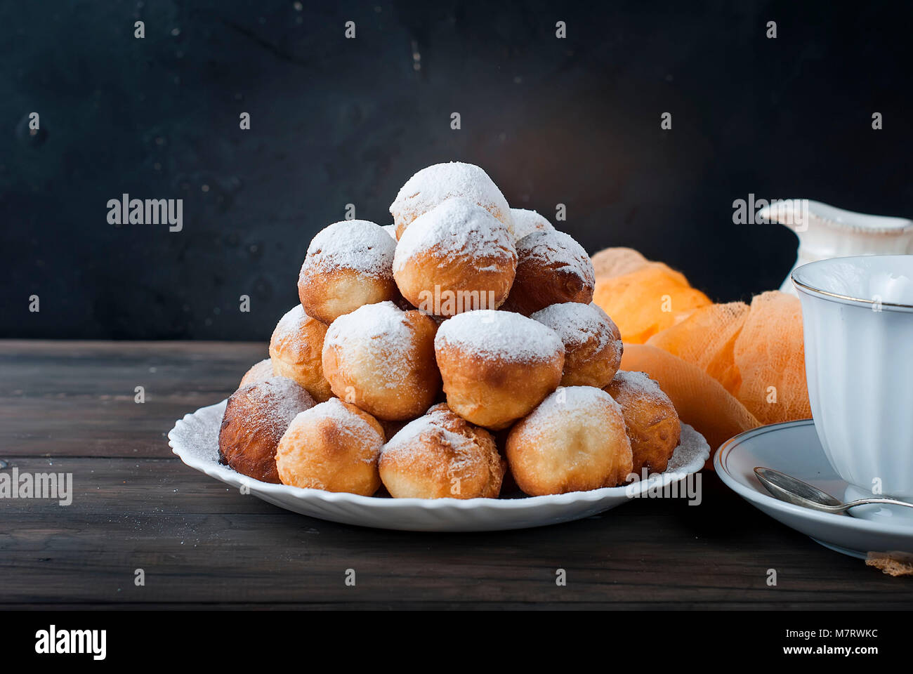 sweet donuts laid out pyramid sprinkled with powdered sugar on the plate , Milk jug and cup, breakfast , on dark - Stock Image